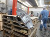 A 304 SST piece waits on top of some pallets to be fully assembled