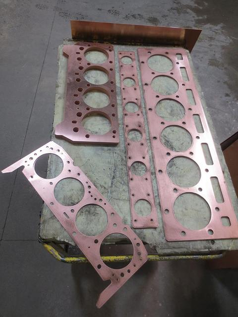 An overhead view of copper head gaskets on top of a moving cart