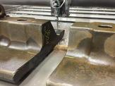 A close up view of a waterjet cutting machined use for cut forging