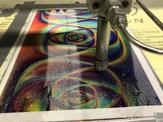 A side view showcasing a holographic sheet being worked on by a high pressure waterjet