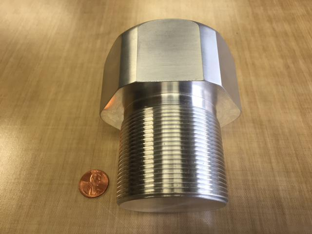 An overhead side comparison of a machined aluminum threaded plug next to a penny