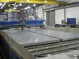 Aluminum plates sit on top of a machine bed waiting to be cut